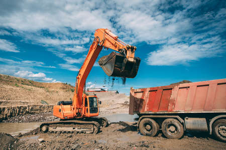 truck: excavator, bulldozer loading dumper truck during highway construction site Stock Photo