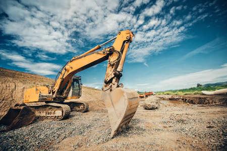 工業用トラック ローダー、地球を移動し、高速道路で道路工事中にダンプカーを読み込み大型スコップで掘削機 写真素材