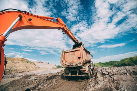 Industrial working excavator loading dumper truck during earthworks, highway construction site and soil transportation