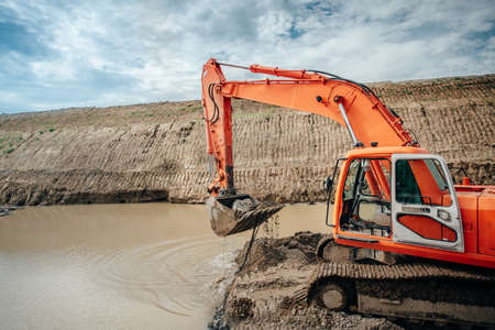 earthmover: Industrial engineer working on excavator during highway construction site, loading dumper trucks and building viaduct and bridge Stock Photo