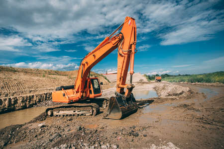 moving truck: industrial excavator in dirt, working on highway construction and building foundation