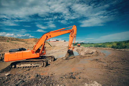 earthmover: industrial excavator working on highway construction site. Details of excavator digging in water and dirt for viaduct construction Stock Photo