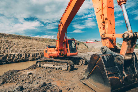 moving truck: Close-up details of excavator scoop during highway construction works. Industry with machinery Stock Photo