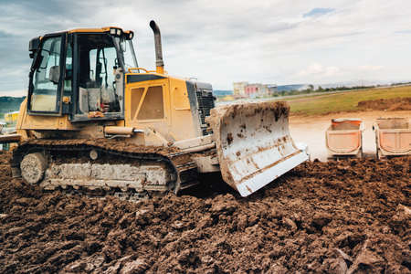 highway construction site development with bulldozer moving earth, soil Stock Photo