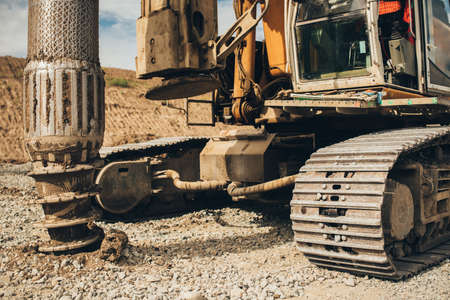Rotary drills working and making holes in the ground on Highway construction site for viaduct and bridge Stock Photo