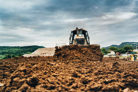 mini bulldozer moving dirt and earth with scoop. Industrial details of landscaping Stock Photo