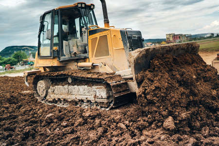 highway construction site with mini bulldozer pushing earth and leveling ground