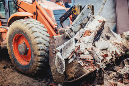 Excavadora de retroexcavadora industrial con cuchara y hoja para cargar escombros de demolición Foto de archivo