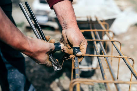 concreting: worker hands using steel wire and pincers to secure steel bars, preparing for concrete pouring on indutrial construction site