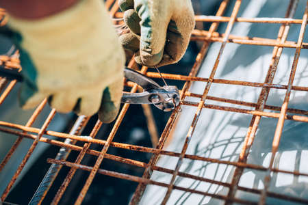 reinforcement: Details of steel reinforcement on construction site. Industrial construction worker using pliers and wire rod Stock Photo
