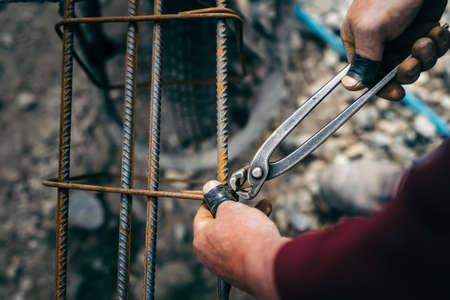 Details of construction worker - hands securing steel bars with wire rod for reinforcement of concrete