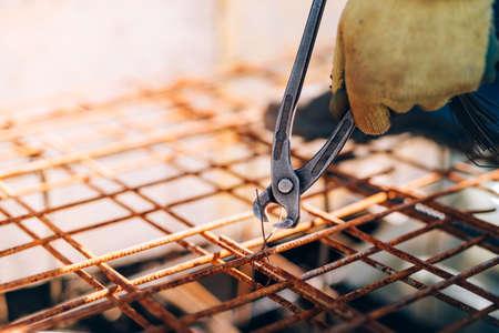 alicates: manos del trabajador de la construcción que usa alicates y barras de acero de seguridad con alambrón para refuerzo de hormigón o cemento Foto de archivo