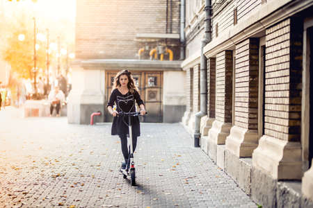 Trendy woman, beautiful brunette girl riding electric scooter in modern city