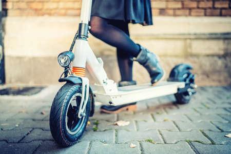 Sluit omhoog details van modern vervoer, elektrische schopautoped, Portret van meisje die het stadsvervoer berijden