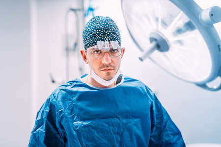Close up portrait of plastic surgeon with surgical scrubs and lamps in operating room Stock Photo
