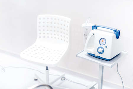 Chair and medical device in hospital room. Surgery suction device
