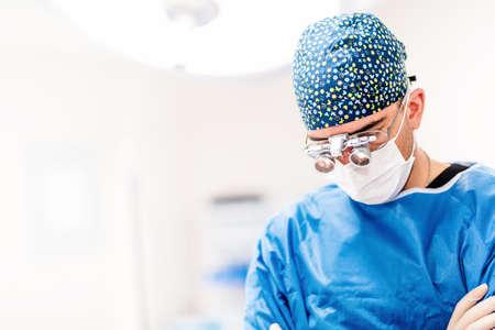 Retrato del cirujano de sexo masculino, plástico plástico mirando hacia abajo con lámparas quirúrgicas en el fondo. Doctor con lupas
