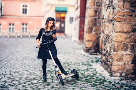 Beautiful young woman writing text message while riding electric scooter on urban streets