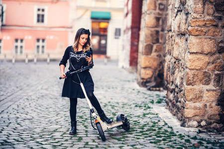 Mooi jong vrouw het schrijven tekstbericht terwijl het berijden van elektrische autoped op stedelijke straten