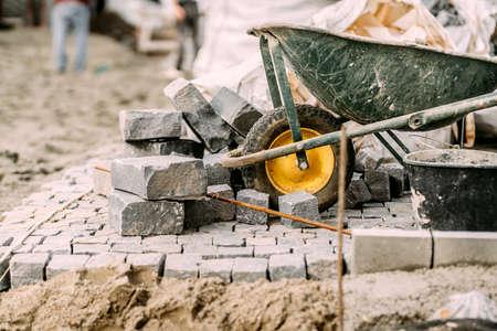 Paving pavement details with granite stones, cobblestock blocks and wheelbarrow on construction site