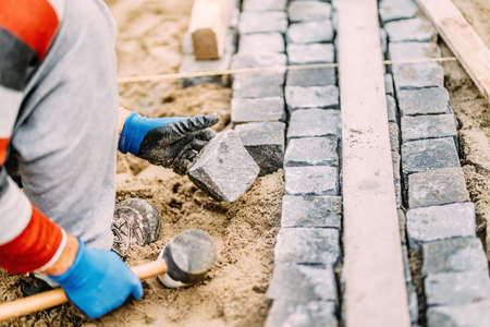 Close up details of construction works with industrial worker placing granite cobblestone blocks on path or alley