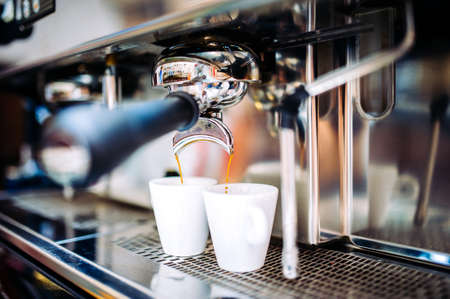 Automatic espresso machine pouring fresh brewed coffee into cups Stock Photo