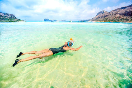 freediving: Portrait of attractive girl wearing swimsuit and snorkling in clear ocean water