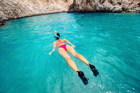 freediving: Snorkeling details, woman looking for coral reef in tropical island