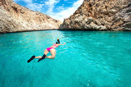 freediving: Traveling and watersports details - wide angle view of woman enjoying swimming and snorkeling