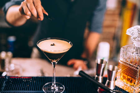 Iced coffee, whiskey based irish cocktail. Close up of bartender hand preparing beverage  Stock Photo