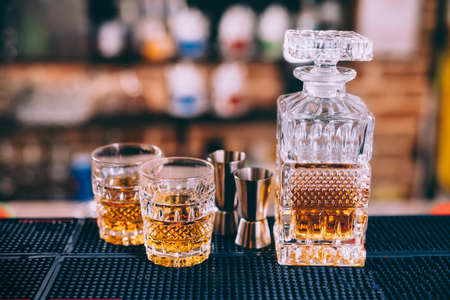 Close up of whiskey bottle, crystal glasses and cocktail tools in modern bar, on counter