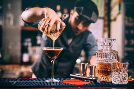 Portrait of professional bartender preparing alcoholic drinks at bar 스톡 콘텐츠
