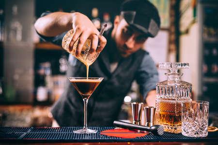Portrait of professional bartender preparing alcoholic drinks at bar Foto de archivo