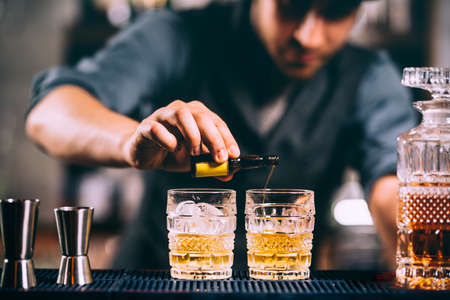 Barman adding cocktail incredients on whiskey cocktails on bar counter Stock Photo