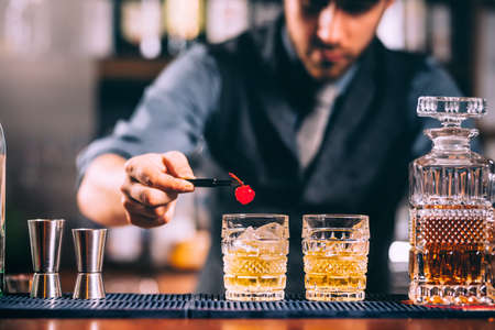 Close up of bartender hands preparing old fashioned whiskey cocktail on bar counter Stock Photo