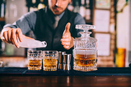 Close up of barman hands adding ice and whiskey to modern urban cocktails. Sky bar serving elegant drinks Stock Photo
