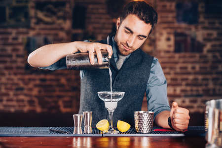 Close up of barman hands adding ice and tequila to modern urban cocktails. Sky bar serving elegant drinks Stock Photo