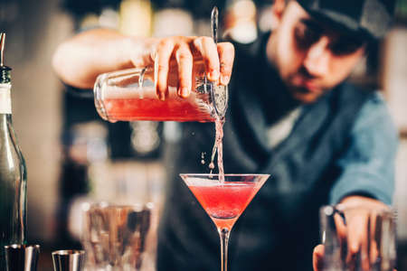 barman preparing and pouring red cocktail in martini class. cosmopolitan cocktail with bar background 스톡 콘텐츠