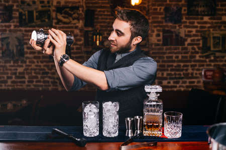 barman using shaker and bartending tools for preparing cocktails