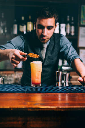 preparation of perfect summer cocktail, orange with cherry and orange slice. Close up of handsome bartender at work Foto de archivo