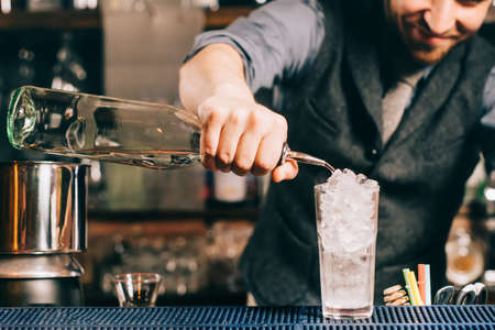 Barman details - pouring rum into drink, alcoholic drink preparation