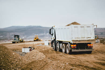 Industrial dumper trucks working on highway construction site, loading and unloading earth. heavy duty machinery activity