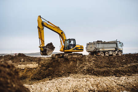 Industrial heavy duty machinery, details of excavator building highway and loading dumper trucks on construction site Stock Photo