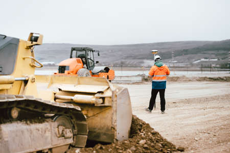 Surveyor engineer with GPS system outdoors at highway construction site, excavator and bulldozer details 스톡 콘텐츠
