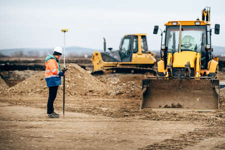 Construction industry details with surveyor using GPS system and total station. Engineer and geodesy