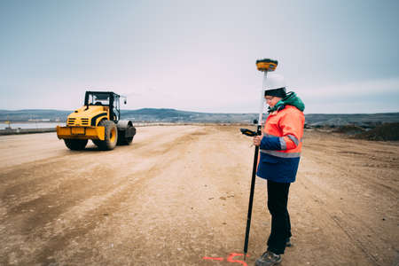Portrait of engineer on construction site, surveyor using gps system and theodolite on highway construction site
