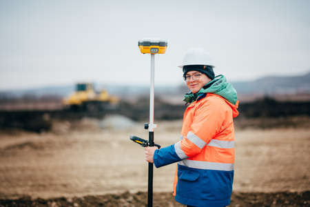 Surveyor engineer working on highway construction site, working with theodolite and gps system 스톡 콘텐츠