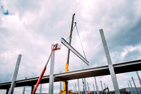 Crane lifting  concrete frameworks, shutterings and heavy prefabricated concrete components at construction site