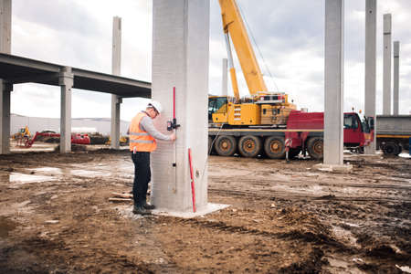survey engineer in prefabricated construction site using special equipment for surveying