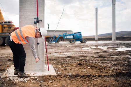 industrial engineer working on building site with cement pillars and surveying tools